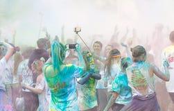 Le participant dans la couleur courent écarter les bras dans le ciel Images stock