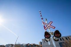 Le passage à niveau nord-américain avec son panneau routier typique, saltire a formé, et les barrières rouges et blanches de barr photo libre de droits