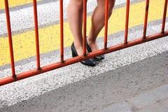 Le passage pour piétons est fermé Les pieds des femmes sont sur le passage piéton devant la barrière photographie stock libre de droits