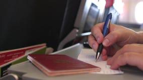 Le passager avec le passeport complète les cartes de migration ou d'arrivée dans le vol plat de moment 3840x2160 clips vidéos