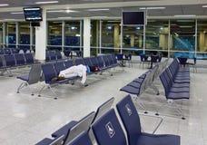 Le passager dort sur des sièges dans un aéroport vide de nuit Photo stock