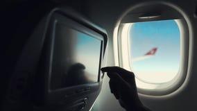 Le passager masculin touche l'affichage dans le siège de la carlingue de l'aéroport, plan rapproché de main clips vidéos