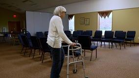 Le passeggiate senior della donna hanno andato per radrizzare su tappeto con l'assistenza di un camminatore stock footage