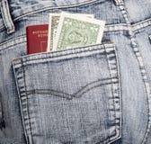 Le passeport russe et deux notes sur un dollar dans une hanche-poche Photographie stock libre de droits