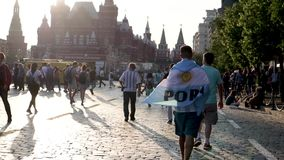 Le passioné du football de l'Argentine de coupe du monde du football avec le drapeau descend la place rouge banque de vidéos