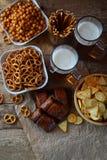 Le passioné du football a placé avec des tasses de bière et de casse-croûte salés sur le fond en bois Les biscuits, bretzel, pail Images libres de droits
