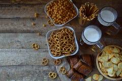 Le passioné du football a placé avec des tasses de bière et de casse-croûte salés sur le fond en bois Les biscuits, bretzel, pail Photos stock