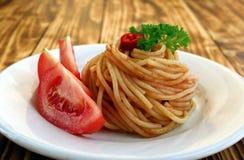 Le paste italiane con il pomodoro e la salsa hanno turbinato in una spirale fotografia stock