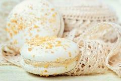 Le pastel a coloré le macaron avec le ruban de dentelle de vintage sur le fond clair Photographie stock