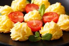 Le patate di duchessa sono servito con la menta ed il primo piano dei pomodori sulla a plat fotografie stock libere da diritti