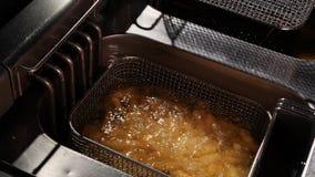 Le patate fritte cominciano friggere in un cesto metallico video d archivio
