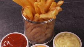 Le patate fritte deliziose sono servito con varietà della salsa stock footage