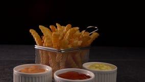 Le patate fritte sono servito in piccolo canestro di frittura con una varietà di tre salse archivi video