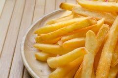 Le patate fritte spruzzate salano sul piatto di legno Fotografie Stock