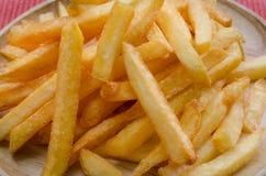 Le patate fritte spruzzate salano sul piatto di legno Fotografie Stock Libere da Diritti