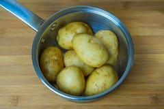 Le patate lavate sono piegate in una pentola d'acciaio La preparazione delle patate prima del trattamento termico successivo Fotografia Stock Libera da Diritti