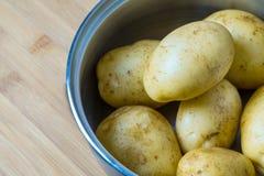 Le patate lavate sono piegate in una pentola d'acciaio La preparazione delle patate prima del trattamento termico successivo Immagini Stock Libere da Diritti