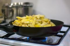 Le patate sono fritte su una stufa di gas fotografie stock libere da diritti
