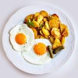 Le patatine fritte hanno fritto le fette della patata con due uova fritte Immagine Stock