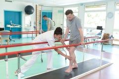 Le patient de aide de beau physiothérapeute établissent sur le tapis roulant photo stock