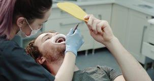 Le patient dentaire moderne de pièce de clinique présentant une garde de bouche après une procédure d'hygiène buccale vont voir u banque de vidéos