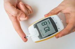 Le patient diabétique surveille le niveau de glucose du sang du doigt photographie stock libre de droits