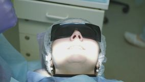Le patient est disposé pour la chirurgie et a mis dessus un chapeau spécial et des verres pour la protection 4K 3840x2160 clips vidéos