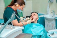Le patient fâché avec des dentis dans le bureau dentaire vérifie des dents Photo libre de droits