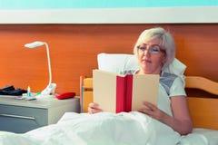 Le patient féminin en verres lit un livre, tout en se situant dans Image stock