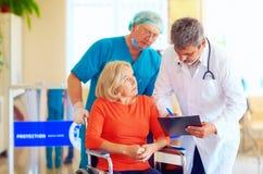 Le patient féminin mûr sur le fauteuil roulant écoute le médicament de prescription de docteur Photos libres de droits