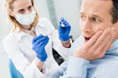 Le patient masculin a peur du dentiste dans moderne photos stock