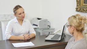 Le patient supérieur féminin dit le docteur au sujet de ses plaintes de santé banque de vidéos