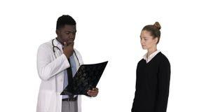 Le patient vient pour soigner avec le physioth?rapeute de rayon de x expliquant le rayon X au patient sur le fond blanc images libres de droits