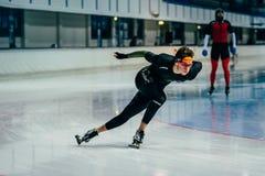 Le patineur d'athlète de jeune homme roule par la piste de courbe pendant l'échauffement Images stock