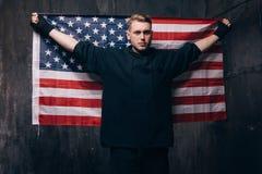 Le patriote fatigué des Etats-Unis tient le drapeau national Image stock