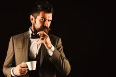 Le patron avec la barbe fume le cigare avec la tasse de café photos stock