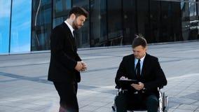 Le patron Businessman indiquent des indications à son employe handicapé par débronchement d'écrire sur le comprimé clips vidéos