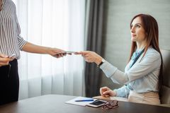Le patron femelle amical donne une note à sa fille auxiliaire discutant des tâches dans le bureau photo stock