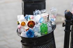 Le pattumiere della via sono riempite di bidoni della spazzatura con le bottiglie di plastica delle ricerche fino alla cima Immagine Stock