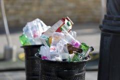 Le pattumiere della via sono riempite di bidoni della spazzatura con le bottiglie di plastica delle ricerche fino alla cima Immagini Stock