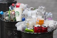 Le pattumiere della via sono riempite di bidoni della spazzatura con le bottiglie di plastica delle ricerche fino alla cima Fotografie Stock