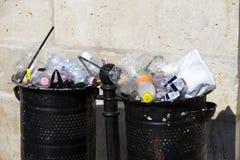 Le pattumiere della via sono riempite di bidoni della spazzatura con le bottiglie di plastica delle ricerche fino alla cima Fotografia Stock