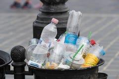 Le pattumiere della via sono riempite di bidoni della spazzatura con le bottiglie di plastica delle ricerche fino alla cima Immagini Stock Libere da Diritti