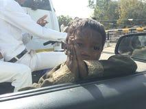 Le pauvre enfant indien prient à la voiture à l'intérieur des personnes disent me donnent svp l'argent Photos stock