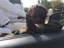 Le pauvre enfant indien prient à la voiture à l'intérieur des personnes disent me donnent svp l'argent Images stock