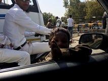 Le pauvre enfant indien prient à la voiture à l'intérieur des personnes disent me donnent svp l'argent Photographie stock libre de droits