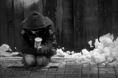 Le pauvre homme prie l'aumône sur un plancher humide et froid au milieu de l'hiver image libre de droits