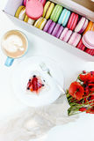Le pavot de matin fleurit le bouquet et les macarons français avec le gâteau et le cappuccino savoureux sur la table blanche Photo stock