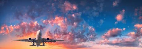 Le paysage avec l'avion de passager vole dans le ciel bleu Photo stock