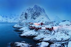 Le paysage d'hiver avec des maisons dans le village, illumination de ville, montagnes neigeuses, mer, ciel nuageux bleu s'est ref photographie stock libre de droits